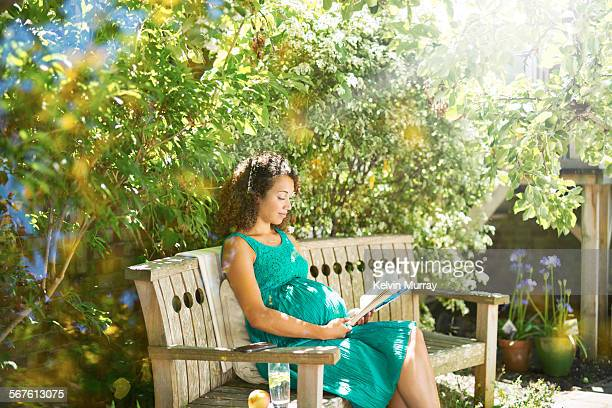 a mixed race pregnant lady relaxes in sunny garden - dress stock pictures, royalty-free photos & images