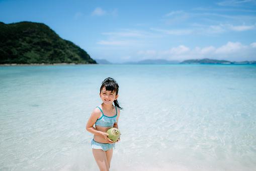 Mixed race preschool girl with coconut on tropical beach, Okinawa, Japan - gettyimageskorea