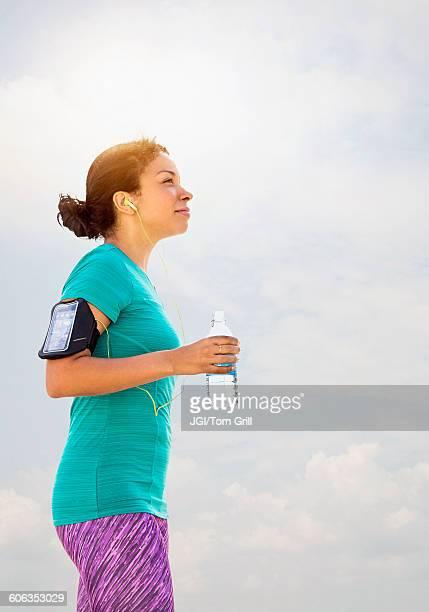 Mixed race runner drinking water outdoors