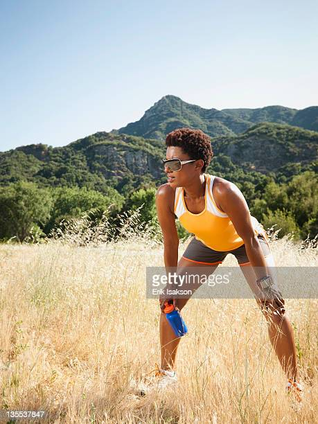 Mixed race runner relaxing in remote field