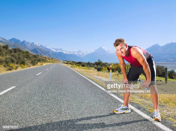 Mixed race runner resting on remote road