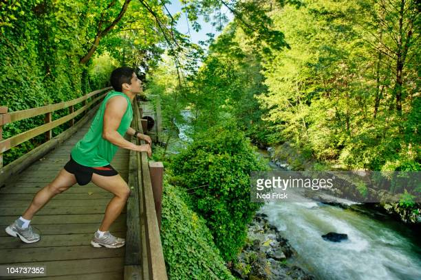 Mixed race runner stretching on walkway near river