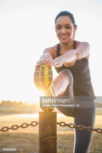 Mixed race runner stretching outdoors