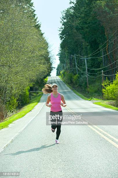 mixed race runner training on remote road - extra long stock pictures, royalty-free photos & images