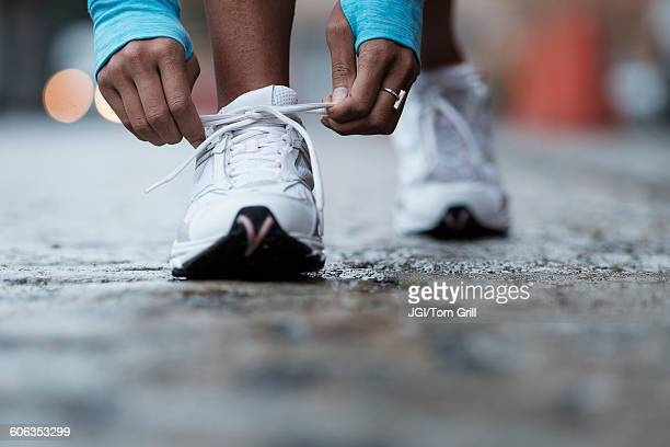 mixed race runner tying shoelaces - tie stock pictures, royalty-free photos & images