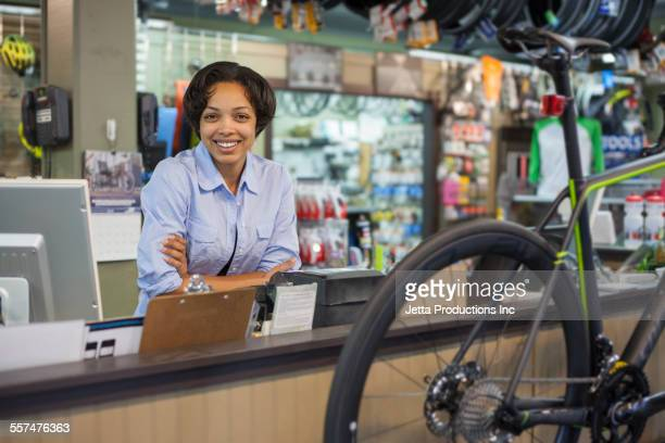 Mixed race saleswoman smiling in bicycle shop