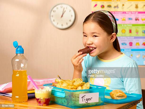mixed race school girl eating junk food - snack stock pictures, royalty-free photos & images