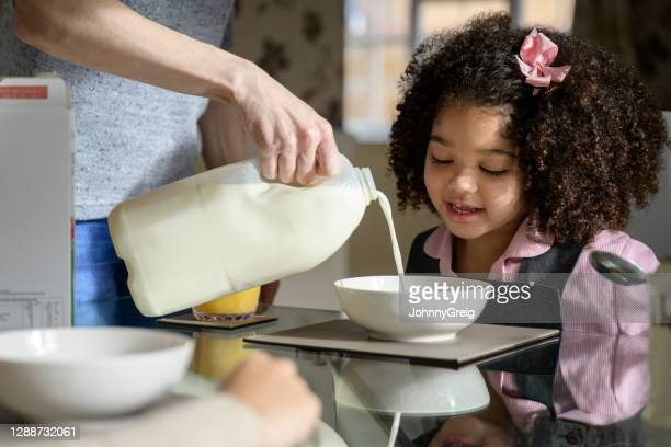 mixed race schoolgirl watching mother pour milk on cereal - primary school child stock pictures, royalty-free photos & images