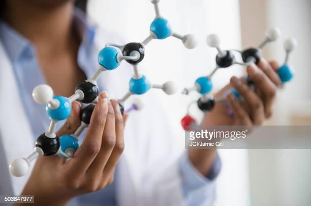 Mixed race scientist examining molecular model