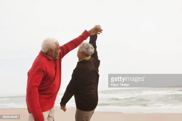Mixed race Senior couple dancing on beach