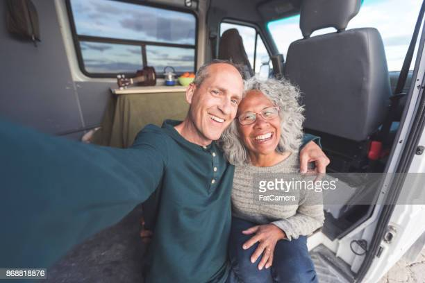 mixed race senior couple takes a selfie in their camper van while on a road trip - interracial wife stock pictures, royalty-free photos & images