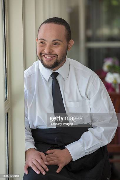 mixed race server with down syndrome smiling in restaurant - somerville massachusetts stock pictures, royalty-free photos & images