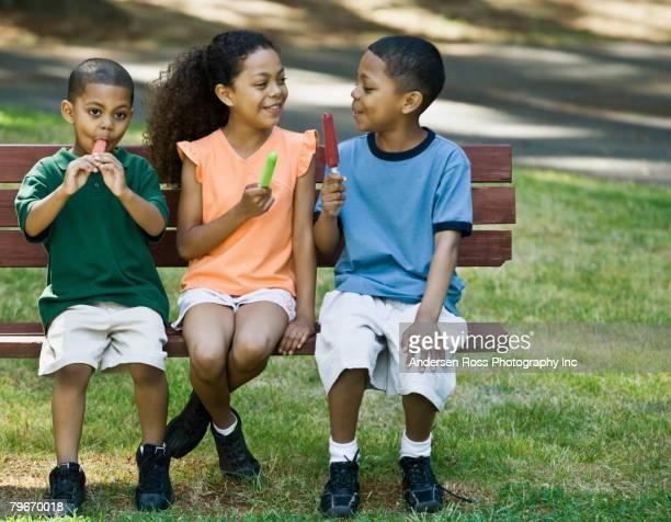 mixed race siblings eating ice pops - somente crianças - fotografias e filmes do acervo