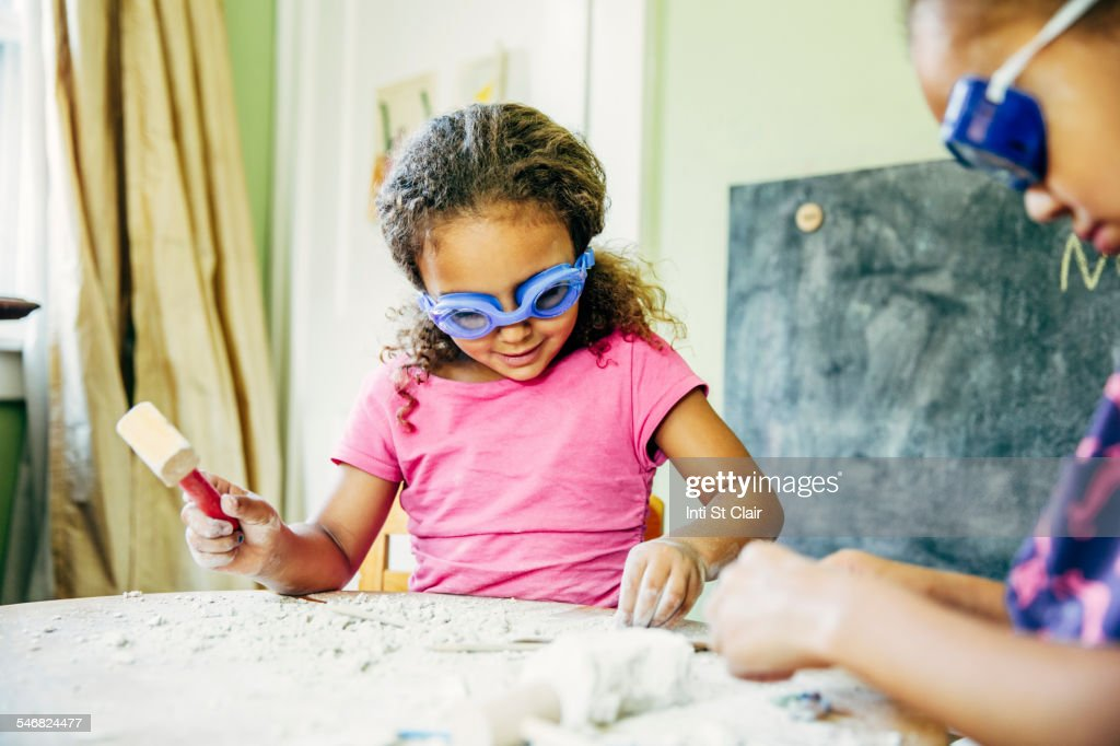 Mixed race sisters doing science experiment at home : Stock Photo