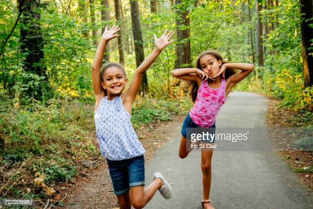 mixed race sisters having fun posing on forest path - funny black girl stock photos and pictures