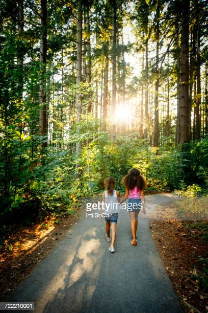 Mixed Race sisters holding hands walking on forest path