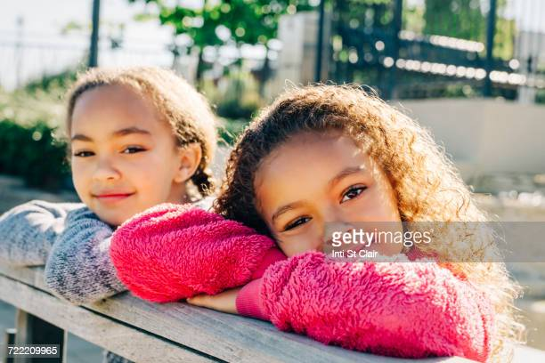 Mixed Race sisters leaning on wooden railing