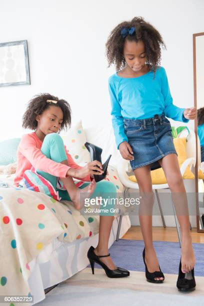 mixed race sisters playing dress up - little girl in high heels stock photos and pictures