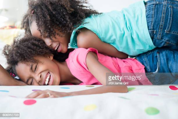 mixed race sisters playing on bed - female wrestling holds stockfoto's en -beelden