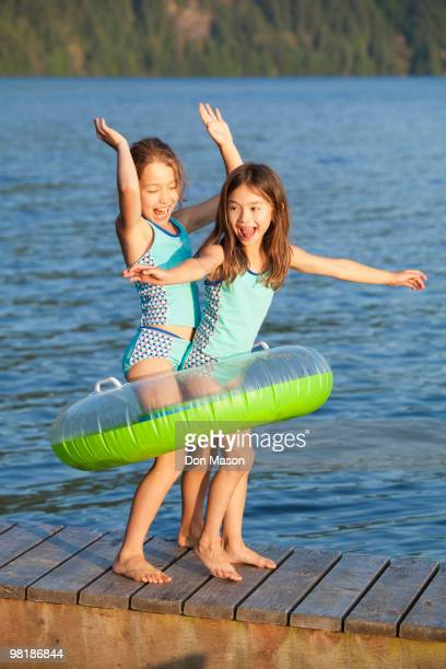Mixed race sisters playing on pier