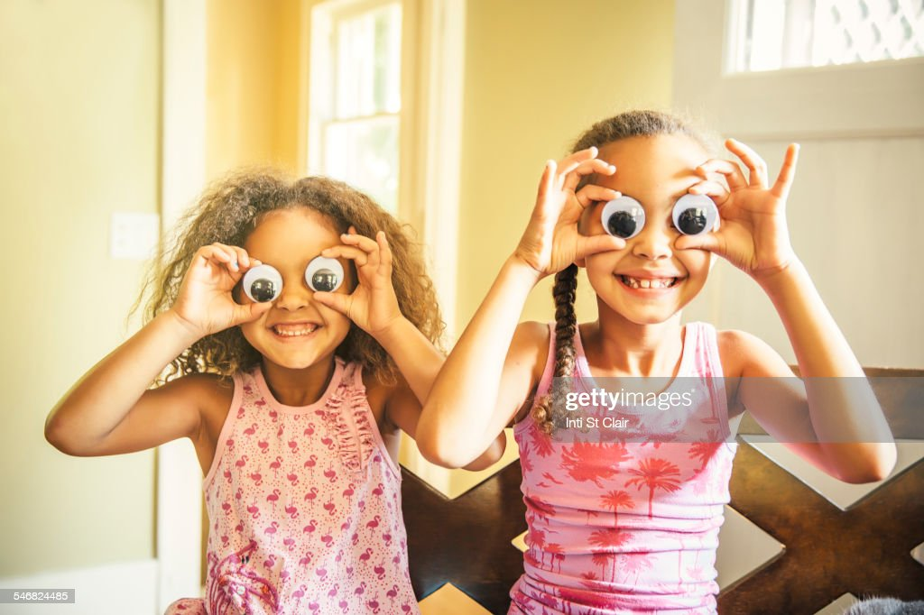 Mixed race sisters playing with googly eyes : Stock Photo