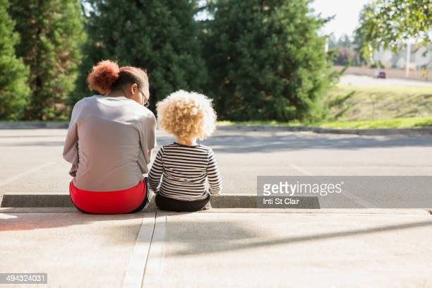 Mixed race sisters sitting outdoors