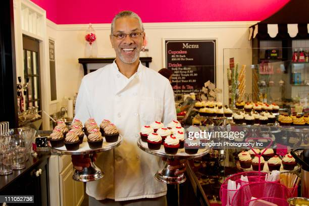 Mixed race small business owner with cupcakes in bakery shop
