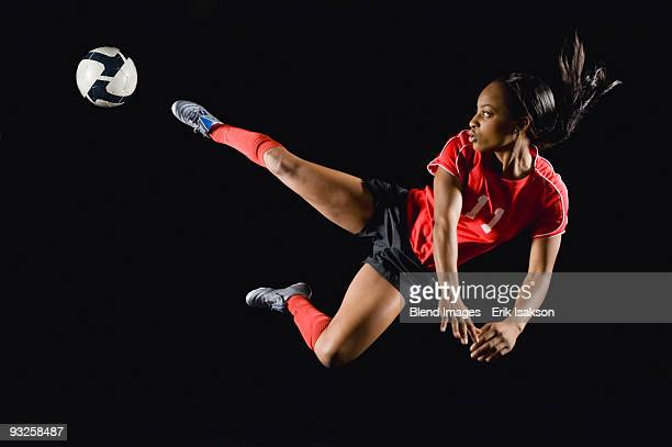 Mixed race soccer player kicking soccer ball in mid-air