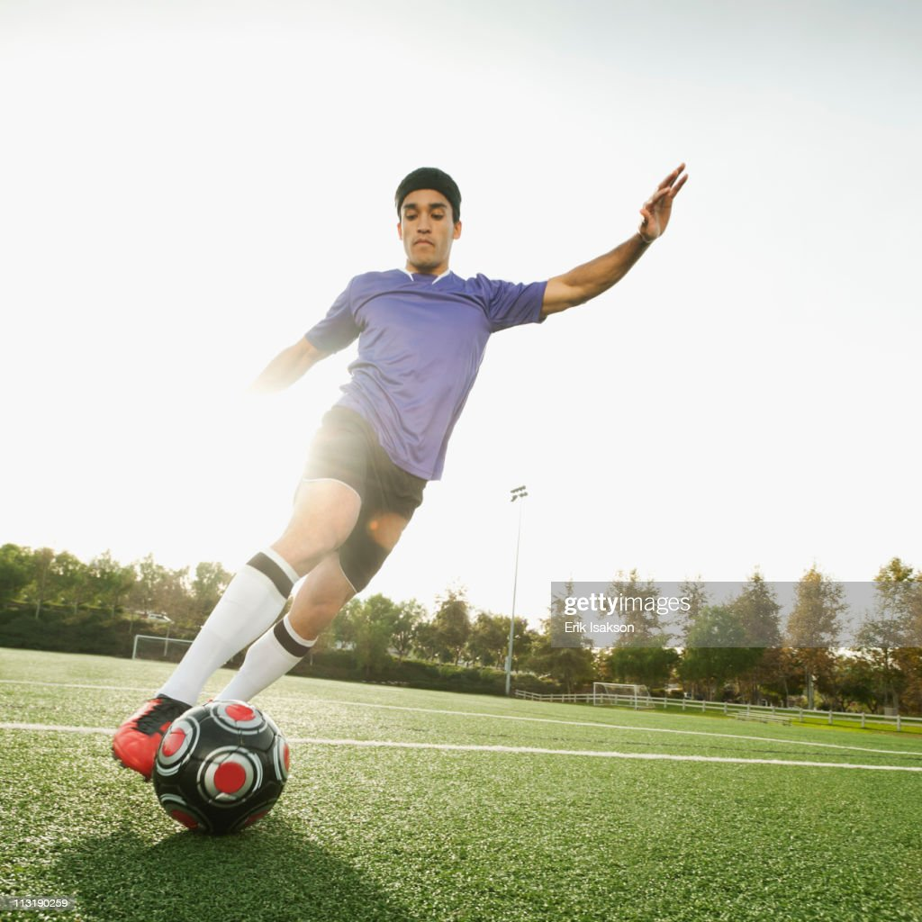 Mixed race soccer player kicking soccer ball : Stock Photo