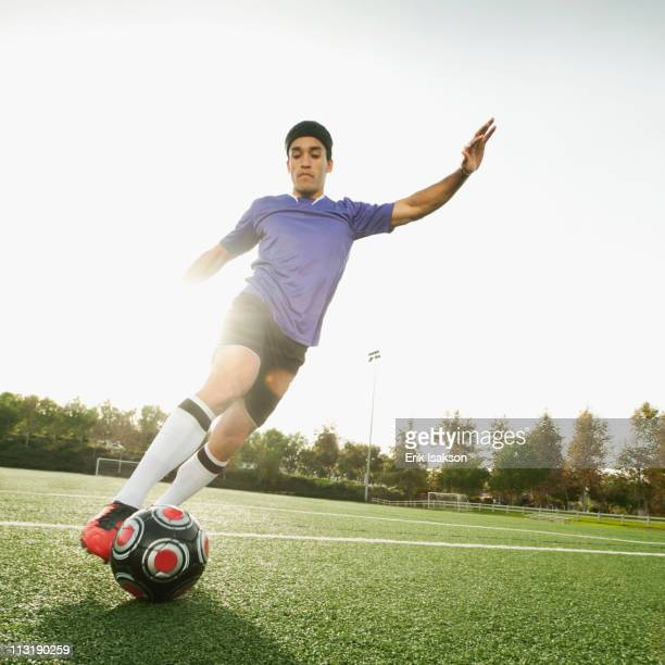 Mixed race soccer player kicking soccer ball