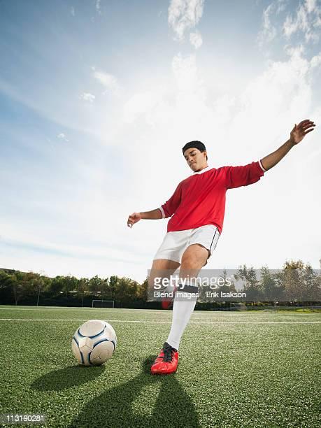 mixed race soccer player kicking soccer ball - ショットを決める ストックフォトと画像