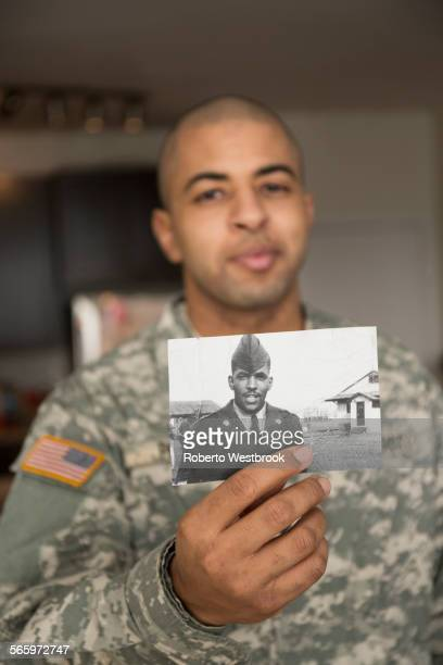 Mixed race soldier holding photograph of father