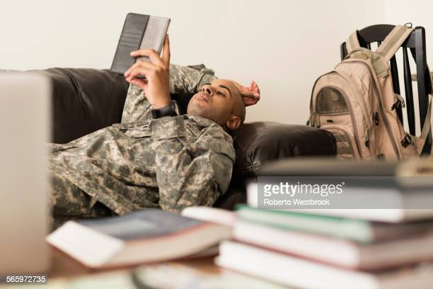 Mixed race soldier using digital tablet on sofa near books