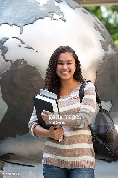 Mixed race student carrying books near globe