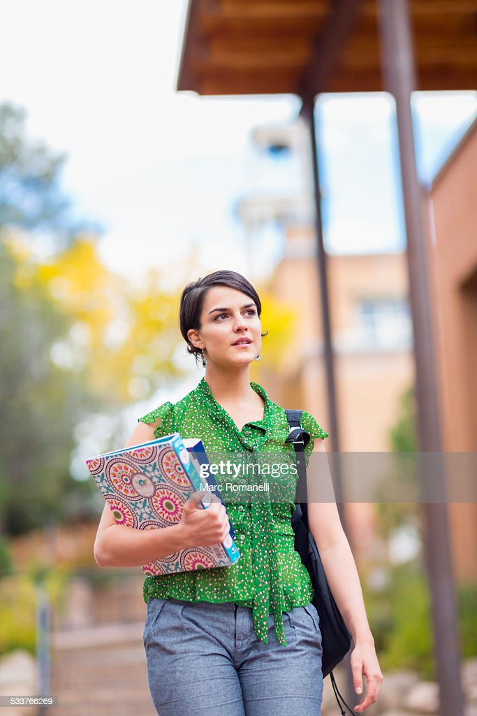 Mixed race student carrying books on campus : Foto stock