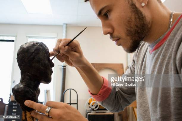 Mixed race student carving wax figure in class