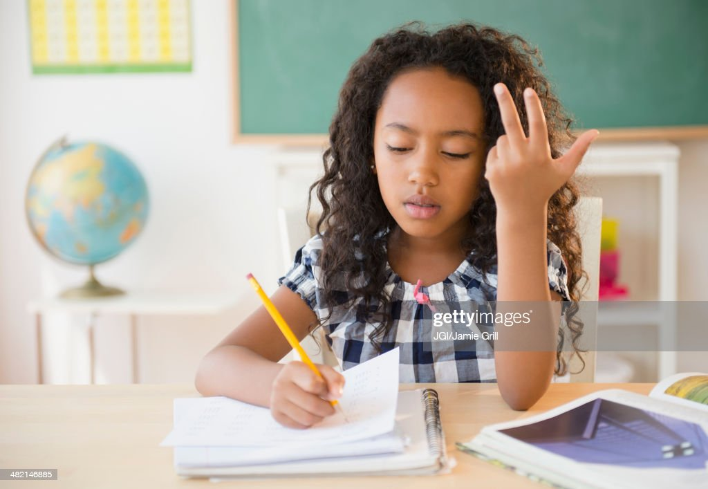 Mixed race student counting on fingers in classroom : Stock Photo