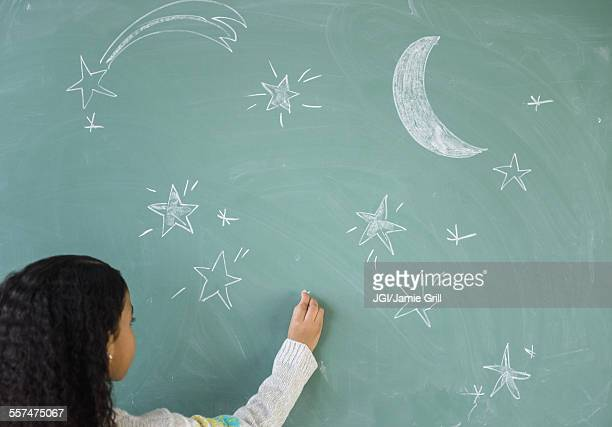 Mixed race student drawing stars on chalkboard in classroom