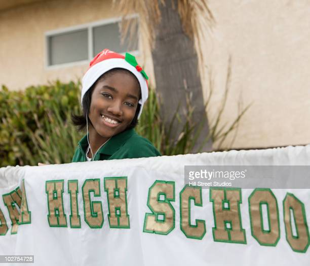 mixed race student holding high school banner - christmas banner stock photos and pictures