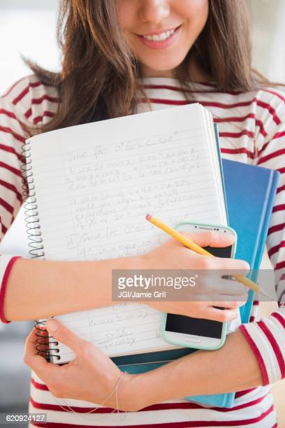 Mixed race student holding homework and cell phone