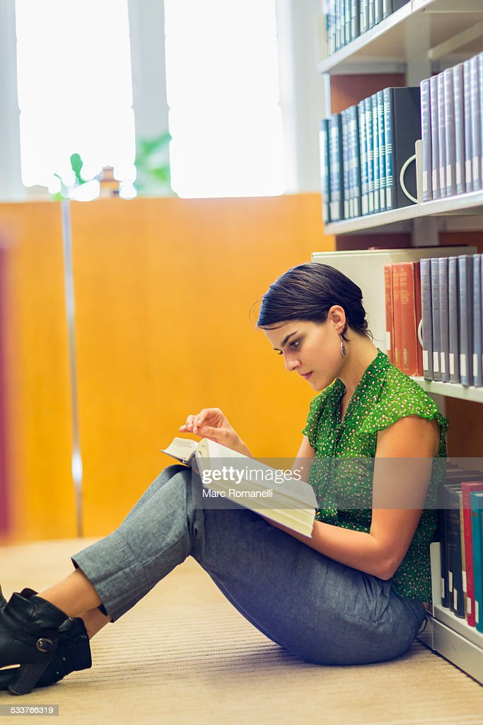 Mixed race student reading book in library : Foto stock