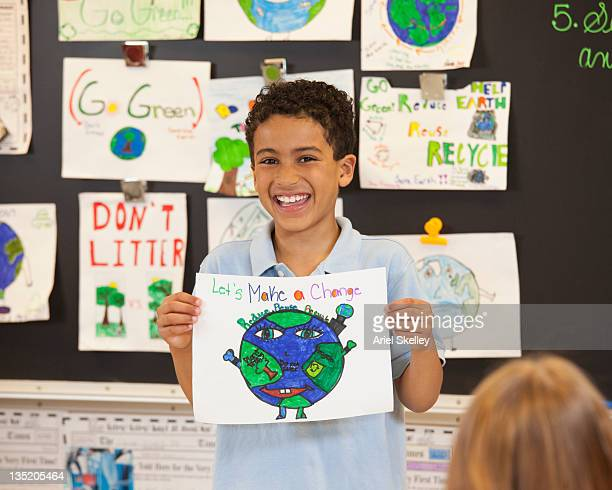 Mixed race student showing globe drawing to classroom