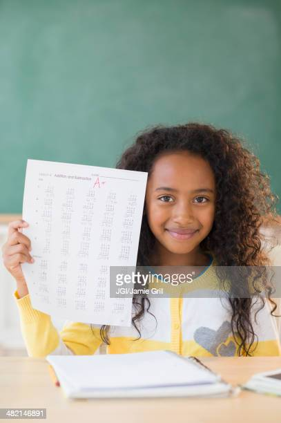 Mixed race student showing off A plus grade in classroom