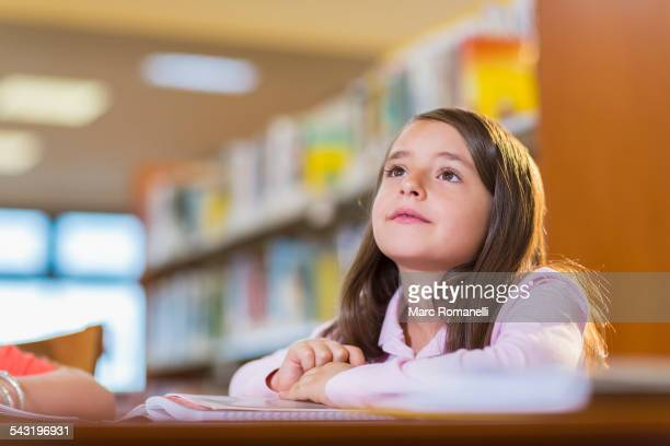 Mixed race student sitting at desk in library