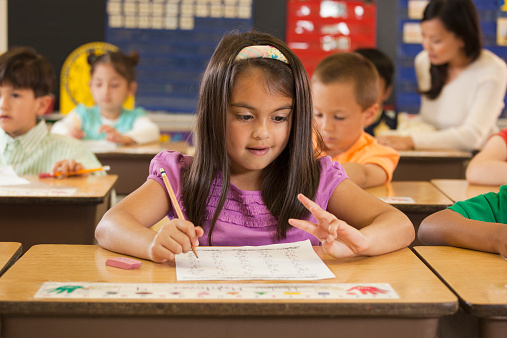 Mixed race student studying at desk in classroom - gettyimageskorea