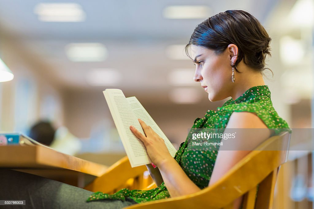 Mixed race student studying in library : Foto stock