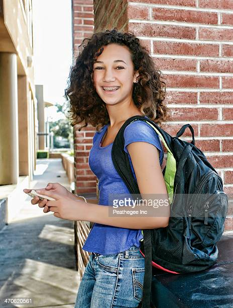 Mixed race student using cell phone
