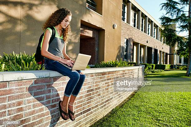 Mixed race student using laptop