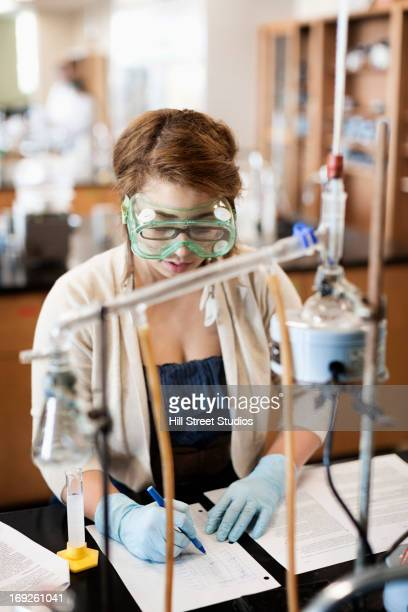 mixed race student working in chemistry lab - bunsen burner stock pictures, royalty-free photos & images