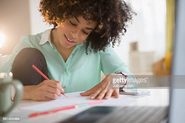 Mixed race student writing notes at desk